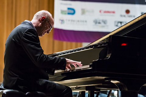 A man in a dark suit playing the piano on stage