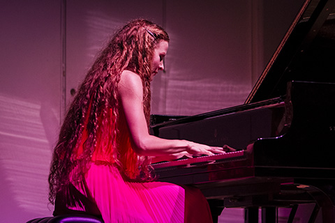 Woman in a red dress playing the piano on stage