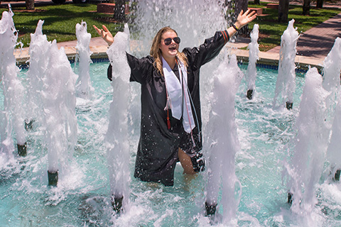 Graduate student celebrating in a fountain on campus