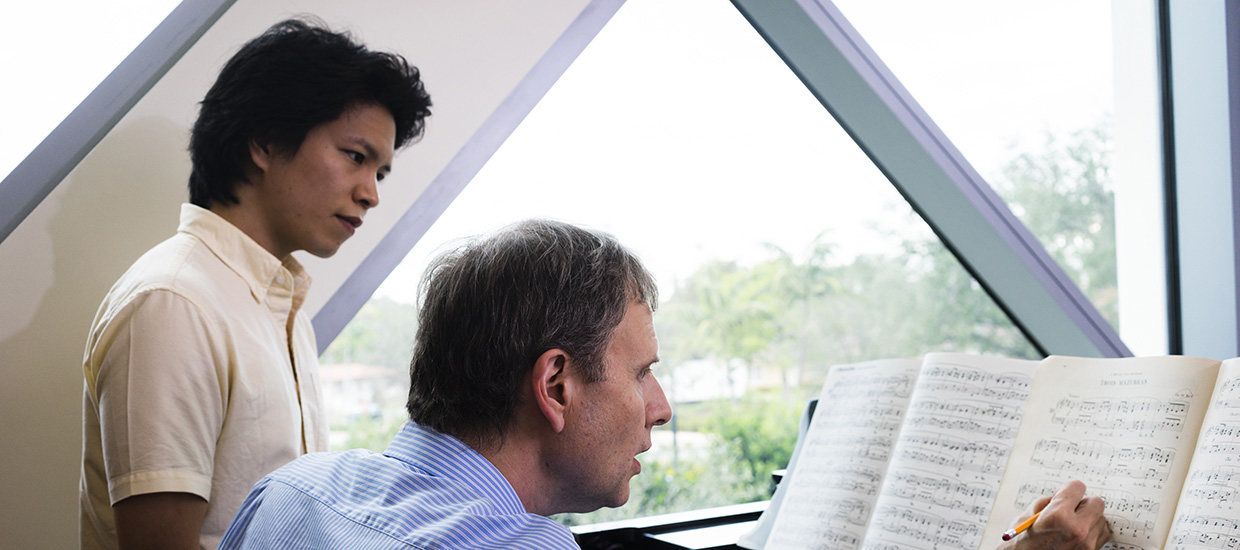 Instructor making notations on sheet music while a student musician looks on