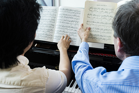 Two people examine sheet music resting on a piano
