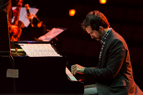 Man looking down as he plays the piano