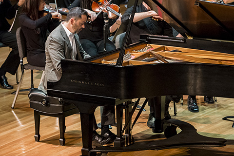 Pianist performs live on stage with orchestral accompaniment